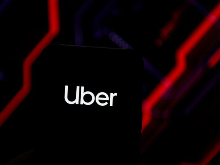 In this photo illustration an Uber logo seen displayed on a